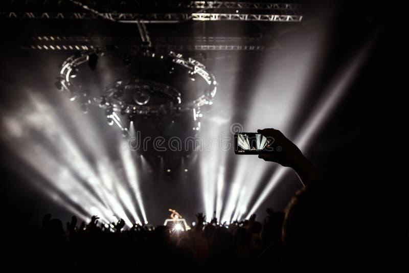有智能手机的手记录实况音乐节日,拍音乐会阶段照片  库存图片