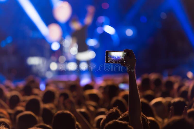 有智能手机的手记录实况音乐节日 库存图片