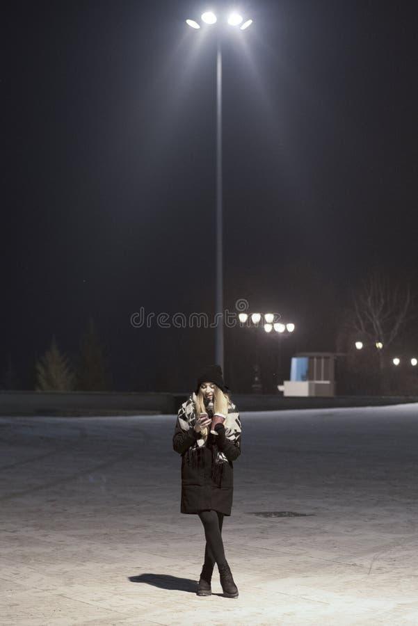 有智能手机的时髦的妇女在街道 免版税图库摄影