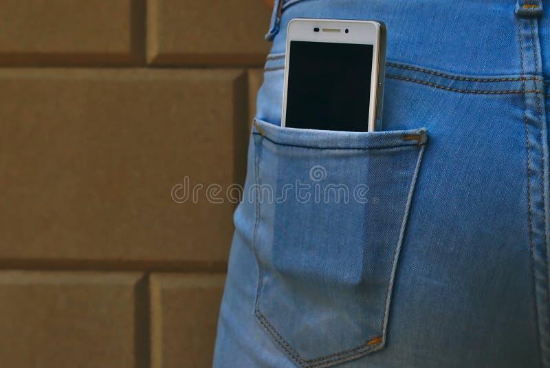 有智能手机的牛仔裤后面口袋 库存照片