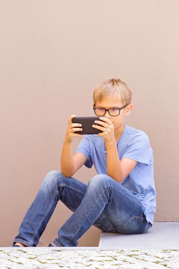 有智能手机的男孩坐室外的台阶 哄骗筛选的观看,读,键入,打比赛 库存照片