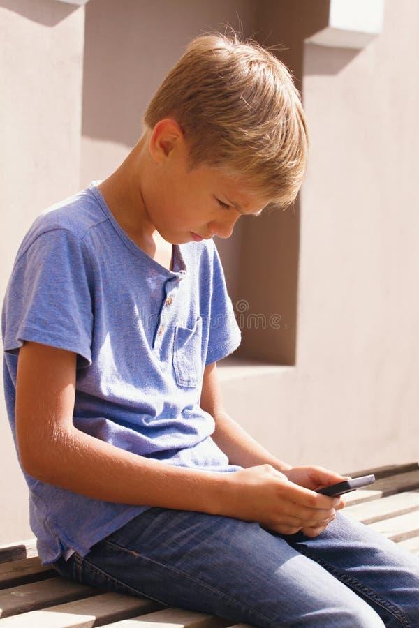 有智能手机的男孩坐室外的台阶 哄骗筛选的观看,读,键入,打比赛 库存图片