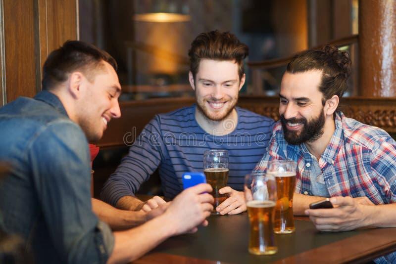 有智能手机的男性朋友喝啤酒的在酒吧 库存照片