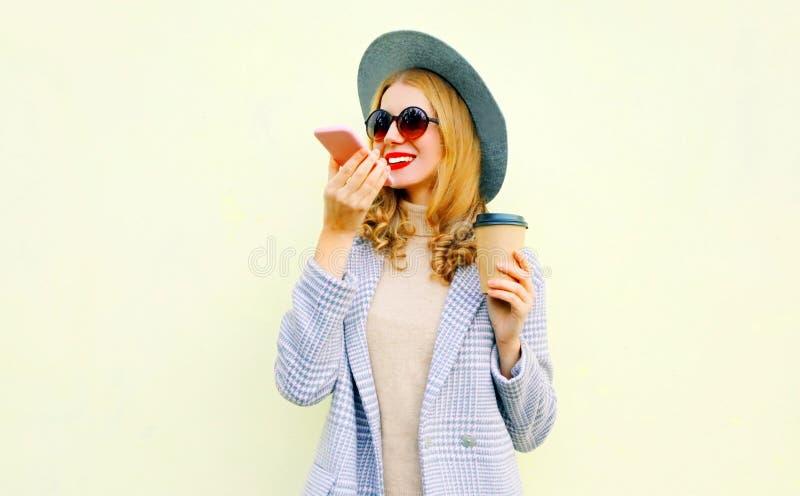 有智能手机的画象愉快的微笑的年轻女人使用声音命令记录器或叫,佩带的外套夹克,在墙壁上的圆的帽子 库存图片