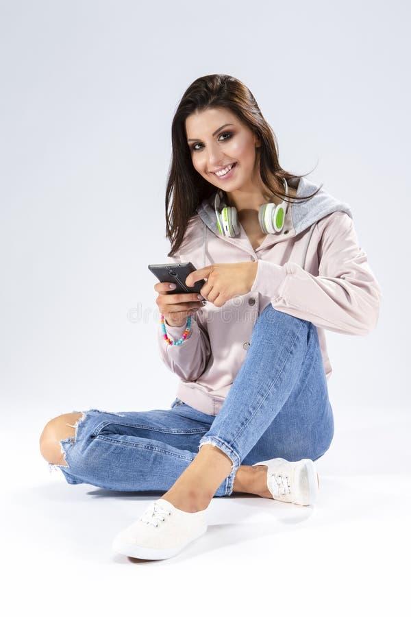 有智能手机的笑的白种人深色的女孩和一个对耳机 坐反对白色的地板 免版税库存照片