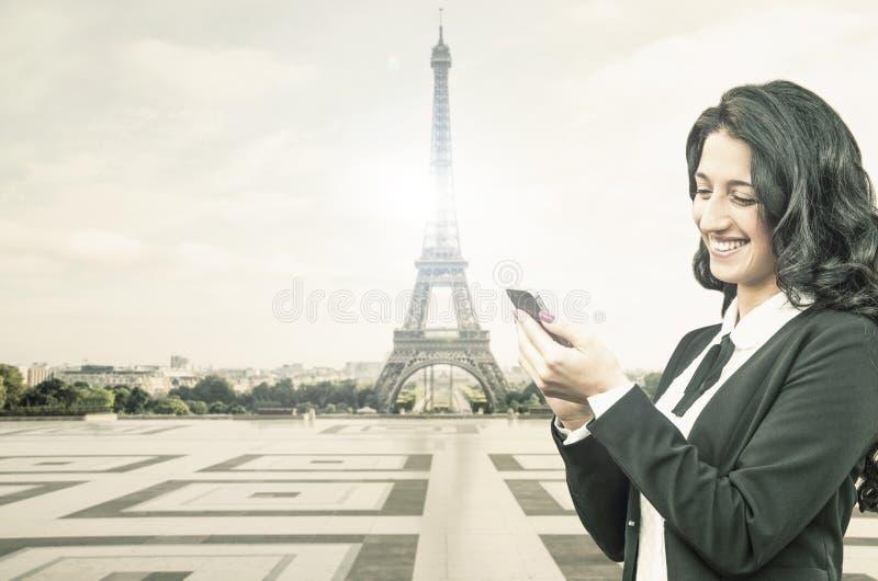 有智能手机的美丽的女孩在艾菲尔铁塔附近 免版税库存图片