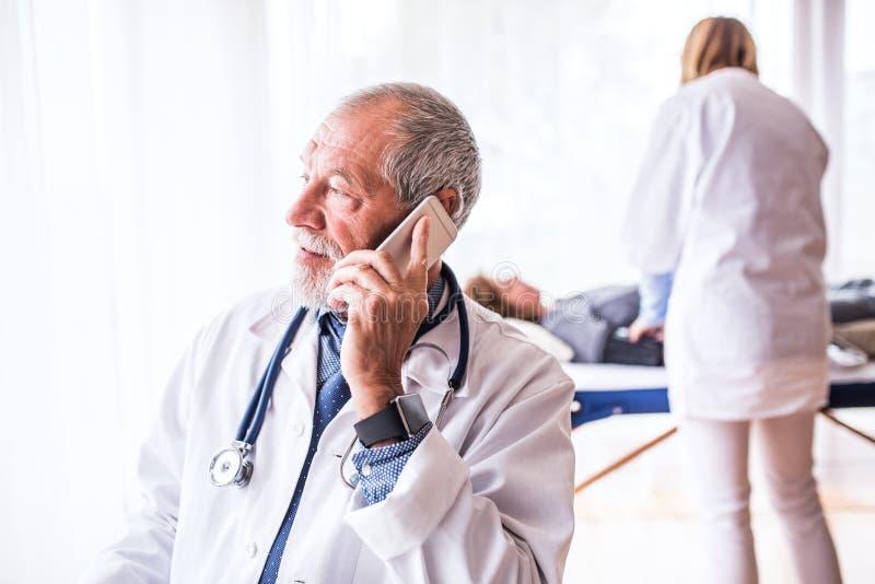 有智能手机的资深医生在他的办公室 免版税库存照片