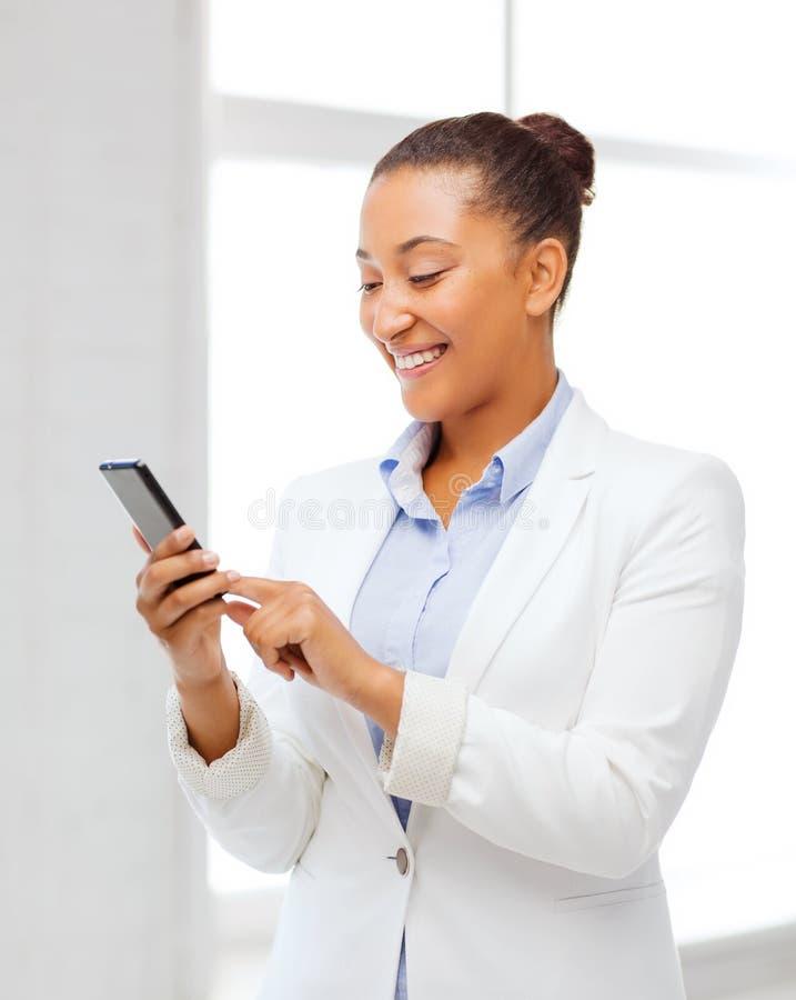 有智能手机的非洲女实业家在办公室 图库摄影