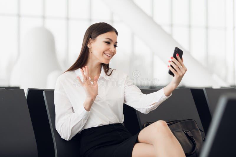 有智能手机的,招呼的挥动的手旅客女实业家在视频通话期间的前面照相机,等待在大厅 图库摄影