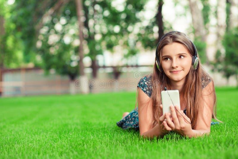???? 有智能手机耳机的愉快的年轻逗人喜爱的学生妇女在听到音乐的头看起来去周道沉思 免版税图库摄影