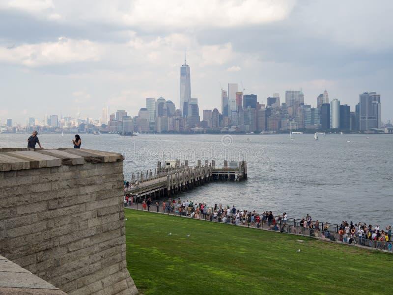 有曼哈顿地平线的自由岛在背景 免版税库存图片