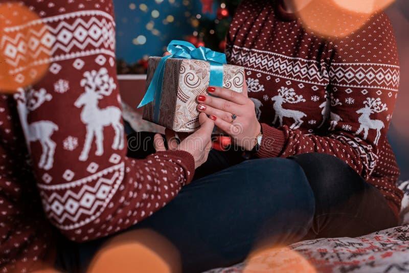 有最高荣誉的礼物盒在浪漫夫妇的手上在圣诞节毛线衣的 库存图片