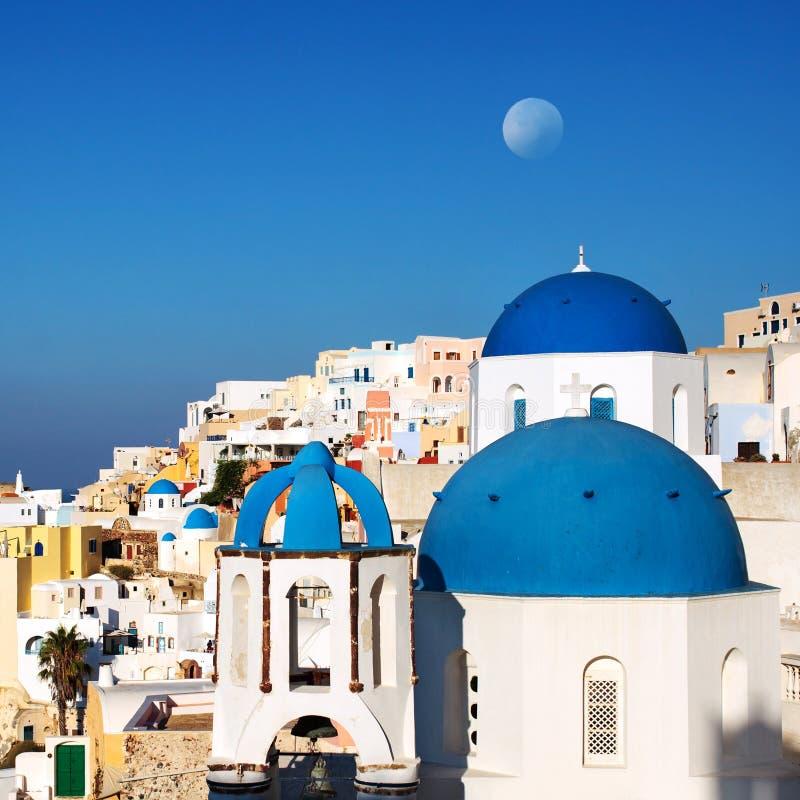 有月亮的圣托里尼蓝色圆顶教会 希腊oia村庄 库存图片