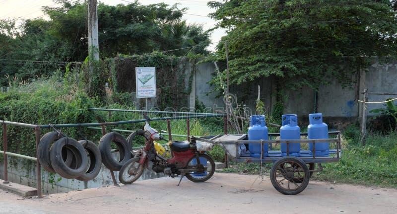 有有三个蓝色制冷剂瓶的推车的老残破的脚踏车 典型的运输 免版税图库摄影