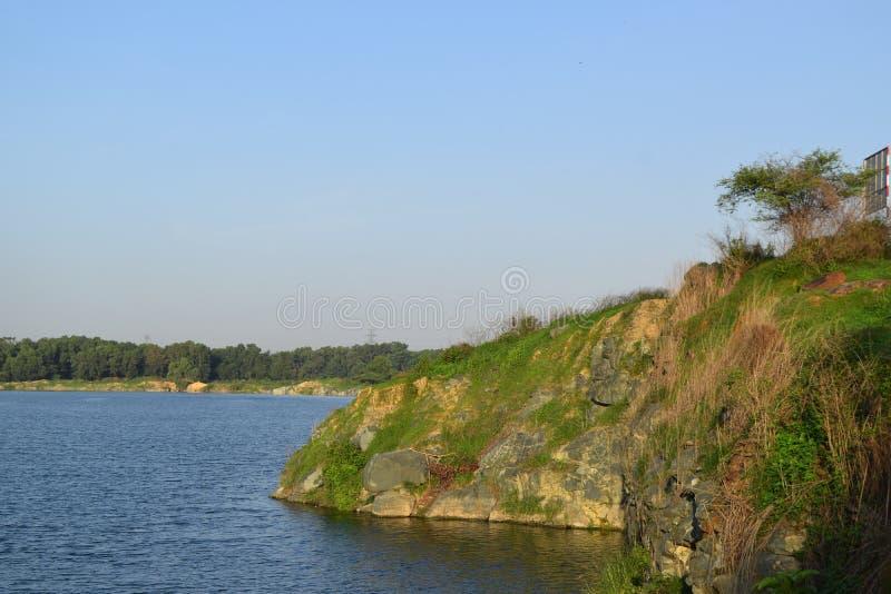 有有些石头的岩石湖和草在银行中 库存照片