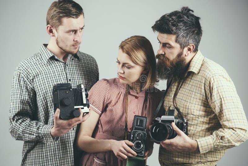 有有些问题 小组有减速火箭的照相机的摄影师 减速火箭的样式妇女和人拿着模式照片照相机 免版税库存照片