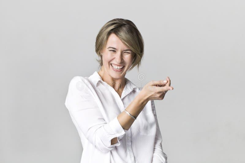 有有吸引力的神色的微笑的正面女性,摆在对白色墙壁的佩带的白色典雅的衬衣 图库摄影