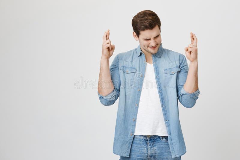 有有希望的表示的渴望宗教者打手势与手指的 牛仔布的不剃须的深色头发的人给结束穿衣 免版税图库摄影