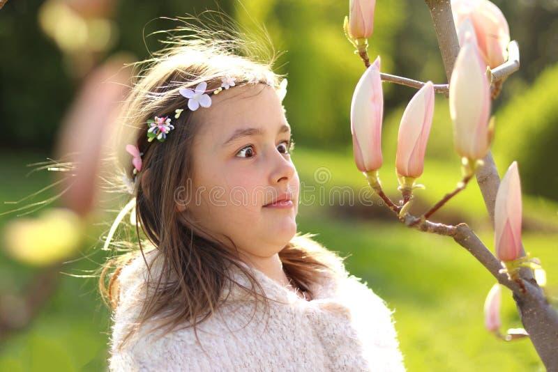 有有手工制造花圈的逗人喜爱的非离子活性剂女孩在有惊奇地看木兰树芽的滑稽的面孔表示的头 免版税库存图片