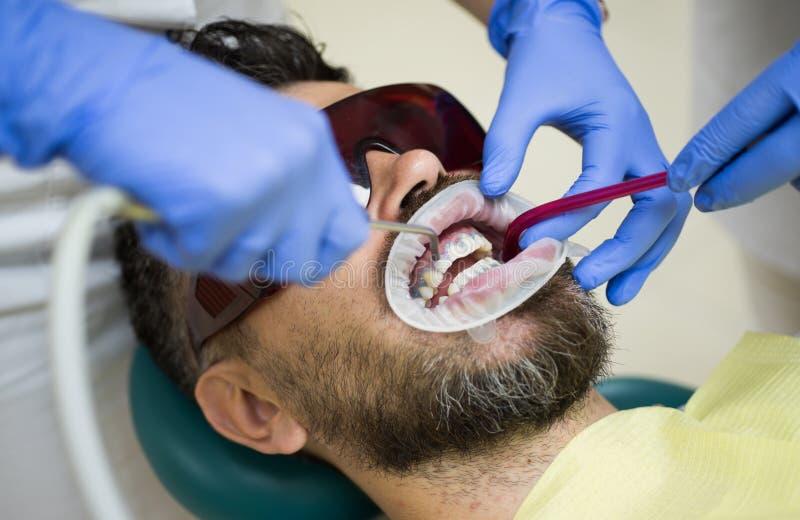 有有胡子的人牙被审查在牙医 关闭人耐心对与坐在医疗的开放嘴的胡子 免版税库存照片
