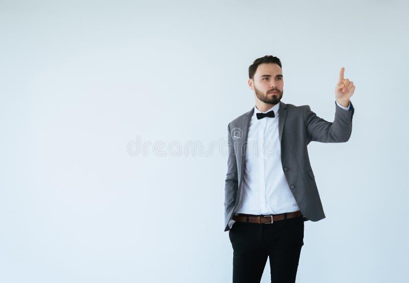 有有胡子的帅哥在正式无尾礼服和衣服陈列手指向某事在白色背景的,复制文本和二的空间 图库摄影