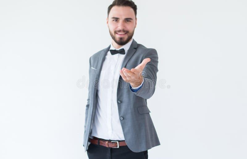 有有胡子的新郎帅哥在正式无尾礼服和衣服陈列手问候和欢迎在白色背景 免版税库存图片