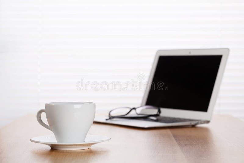 有有膝上型计算机的和咖啡杯的办公室工作场所 免版税库存图片