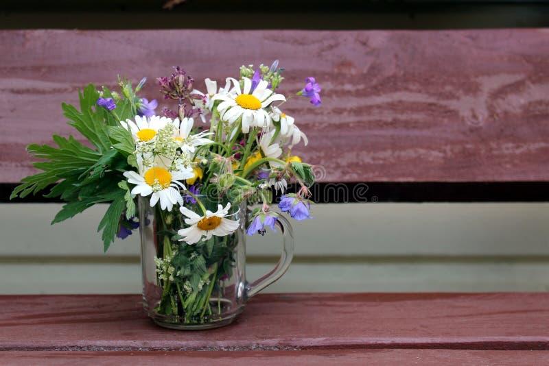 有有野花的一个杯子在桌上 库存照片