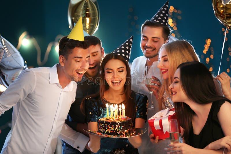 有朋友的年轻女人和在俱乐部的生日蛋糕 库存图片