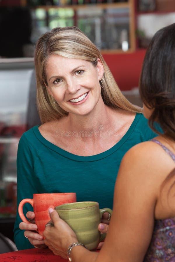 有朋友的微笑的白肤金发的妇女在小餐馆 免版税库存图片
