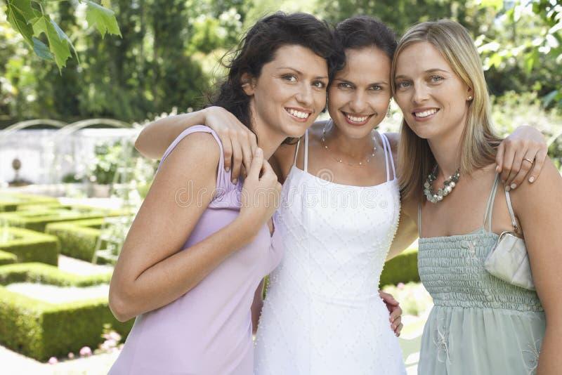 有朋友的愉快的新娘在庭院里 免版税库存照片