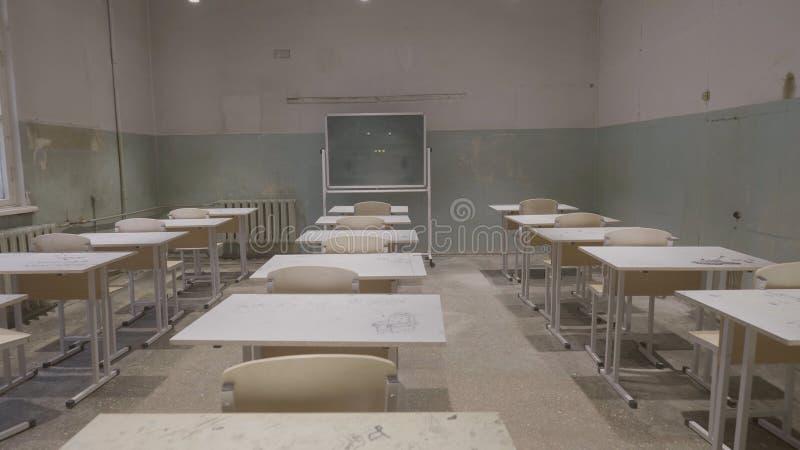 有木书桌,白色和绿色粉笔板的空的教室在学校 空的教室 被放弃的学校教室 库存照片