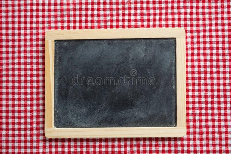 有木制框架的黑板在红色方格的野餐桌布,拷贝空间 库存图片