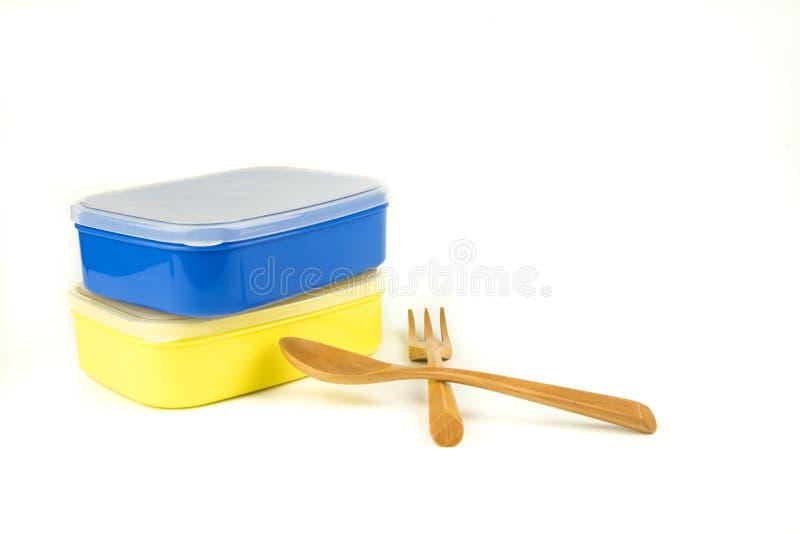 有木匙子的塑料食物在白色的载体和叉子 免版税库存照片