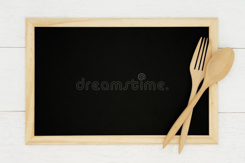 有木匙子的空白的在白色木板条背景的黑板和叉子 免版税库存图片