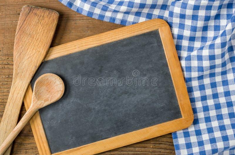 有木匙子的黑板在一张蓝色方格的桌布 库存照片