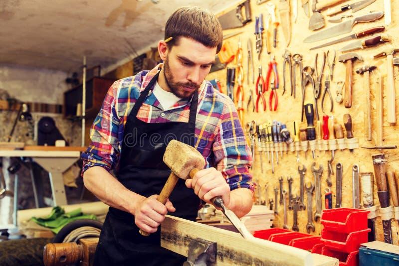 有木头、锤子和凿子的木匠在车间 库存图片