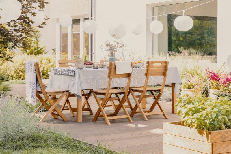 有木庭院家具集合的室外餐厅与桌和椅子 免版税库存照片