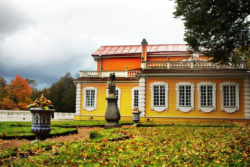 有木房子和庭院雕塑的老庄园住宅 免版税图库摄影