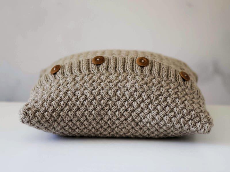 有木按钮的被编织的米黄枕头 库存图片