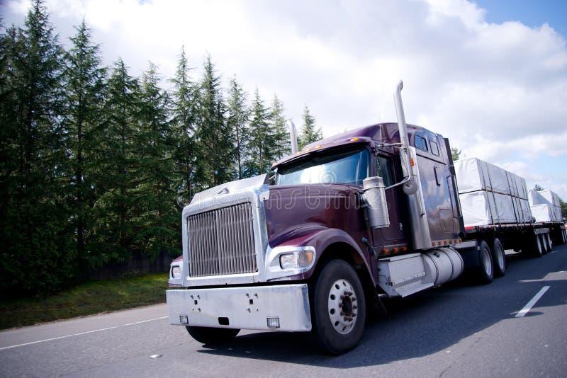 有木材货物的大半船具卡车在平展坏 免版税库存图片