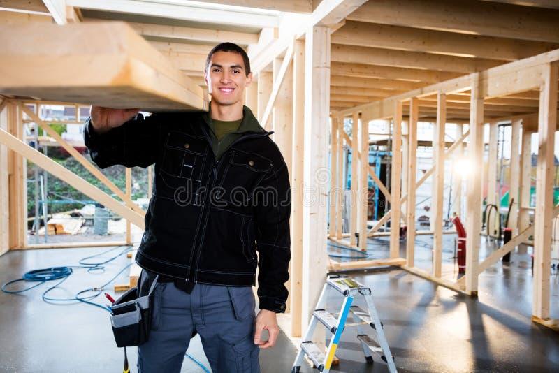 有木板条的男性木匠在建造场所 库存照片