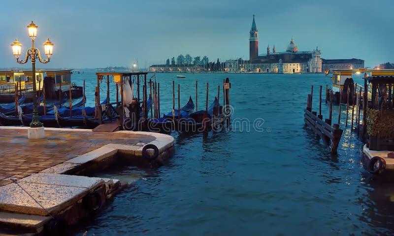 有木栈桥的在威尼斯式近的正方形圣马尔谷教堂的码头和长平底船 圣乔治少校的海岛在背景中 图库摄影
