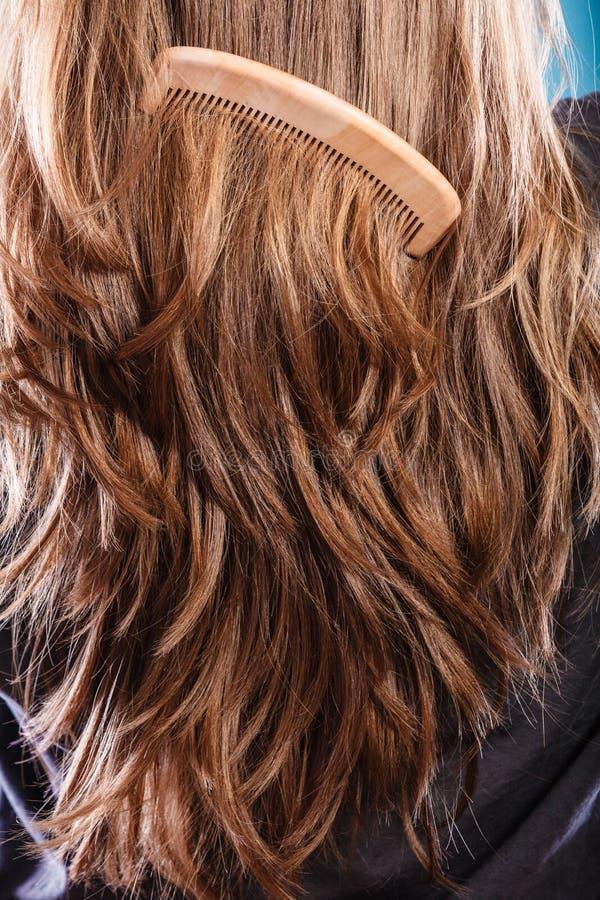 有木梳子特写镜头的平直的棕色头发 免版税图库摄影
