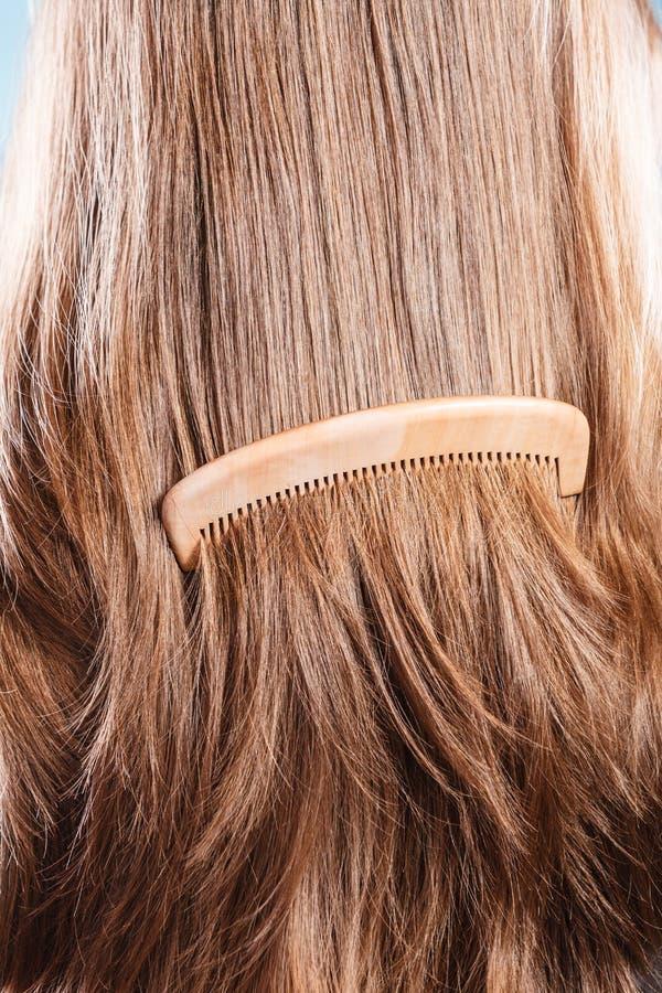 有木梳子特写镜头的平直的棕色头发 免版税库存照片