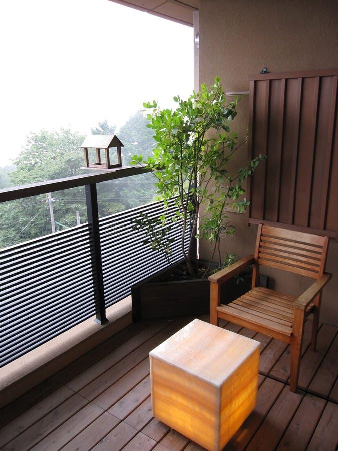 有木椅子、树植物和灯笼灯桌的阳台在日本传统旅馆旅馆 免版税库存图片