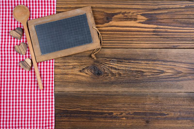 有木烹调匙子的老土气板岩黑板在老木背景的红色白色方格的织品 免版税库存照片