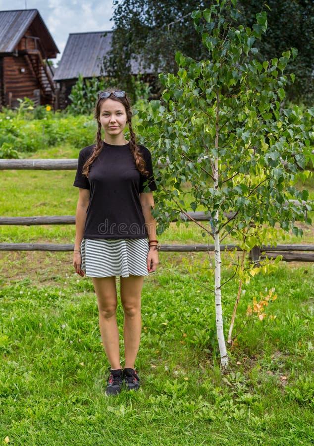 有木犁耙和桶的女孩在乡下公路在村庄 Copyspace 免版税图库摄影