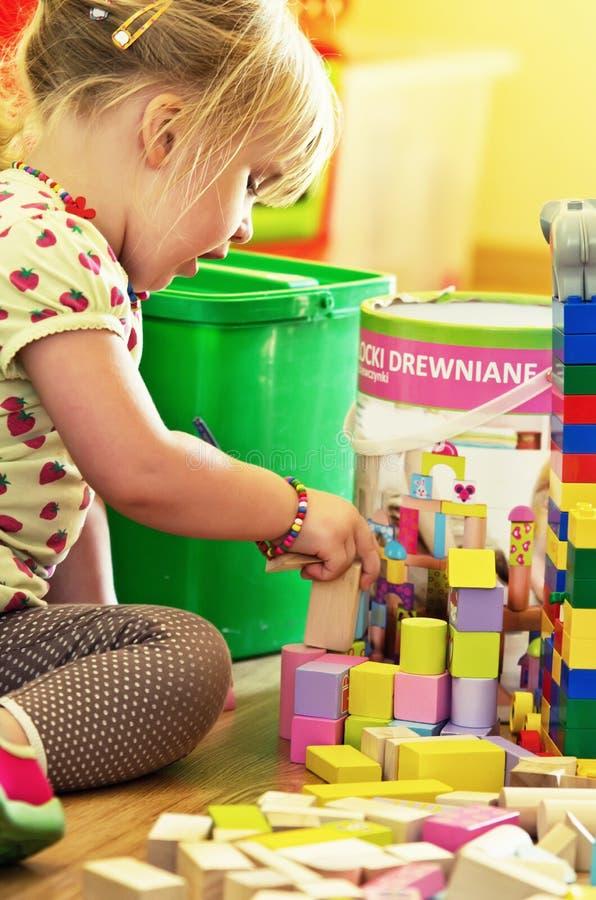有木玩具块的女孩 免版税图库摄影
