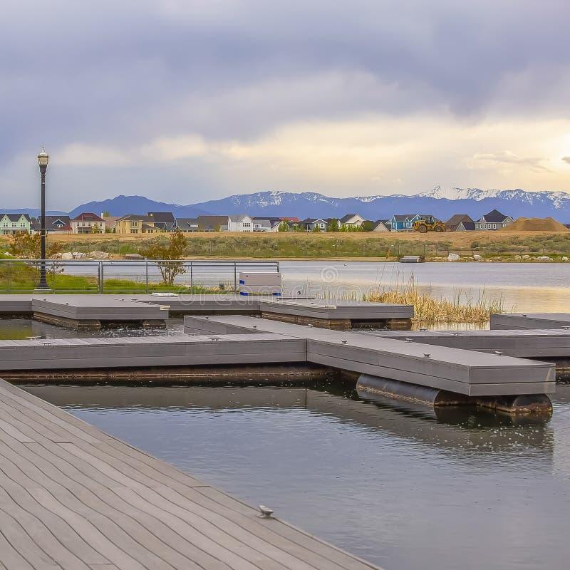 有木甲板的Frame方形的俯视在象草的岸之外的湖和长凳房子 库存图片